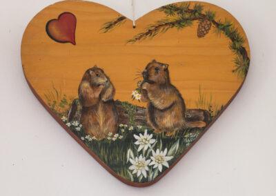 marmottes peintes sur un cœur en bois